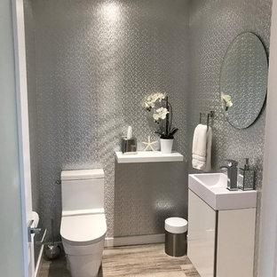 Стильный дизайн: маленький туалет в стиле модернизм с белыми фасадами, унитазом-моноблоком, полом из керамогранита, подвесной раковиной, столешницей из кварцита и коричневым полом - последний тренд