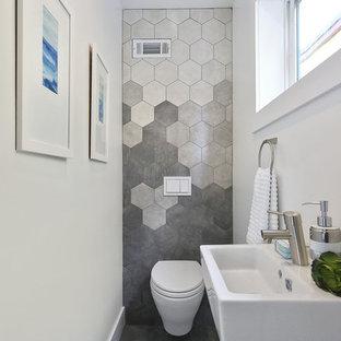 Foto de aseo moderno, pequeño, con sanitario de pared, baldosas y/o azulejos grises, paredes blancas y lavabo suspendido