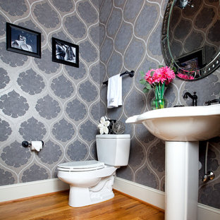 Modelo de aseo minimalista, pequeño, con lavabo con pedestal, sanitario de dos piezas, paredes grises y suelo de madera en tonos medios