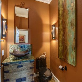 Idee per un piccolo bagno di servizio classico con consolle stile comò, ante con finitura invecchiata, WC monopezzo, piastrelle arancioni, pareti arancioni, parquet scuro, lavabo a colonna, top in granito, pavimento marrone e lastra di pietra