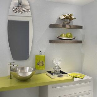 Пример оригинального дизайна: туалет среднего размера в стиле модернизм с плоскими фасадами, серыми фасадами, унитазом-моноблоком, серыми стенами, полом из керамогранита, настольной раковиной, столешницей из искусственного камня, серым полом и зеленой столешницей
