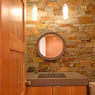 Идея дизайна: туалет среднего размера в стиле модернизм с плоскими фасадами, фасадами цвета дерева среднего тона, унитазом-моноблоком, серой плиткой, каменной плиткой, серыми стенами, полом из бамбука, монолитной раковиной, столешницей из бетона, бежевым полом и серой столешницей