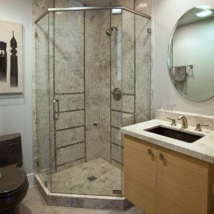 На фото: со средним бюджетом туалеты среднего размера в стиле модернизм с плоскими фасадами, светлыми деревянными фасадами, унитазом-моноблоком, серой плиткой, серыми стенами, полом из керамогранита, врезной раковиной, столешницей из известняка и серым полом