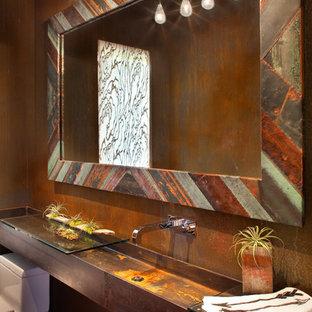 デンバーの大きいラスティックスタイルのおしゃれなトイレ・洗面所 (横長型シンク、無垢フローリング、ガラスの洗面台、一体型トイレ、茶色い壁) の写真
