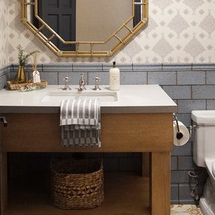 フェニックスのトランジショナルスタイルのおしゃれなトイレ・洗面所 (青いタイル、テラコッタタイル、マルチカラーの壁、テラコッタタイルの床、アンダーカウンター洗面器、マルチカラーの床、グレーの洗面カウンター、壁紙) の写真