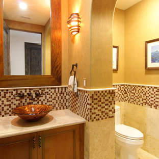Photo of a medium sized mediterranean cloakroom in Los Angeles with recessed-panel cabinets, medium wood cabinets, a one-piece toilet, multi-coloured tiles, mosaic tiles, beige walls, travertine flooring, a vessel sink and limestone worktops.