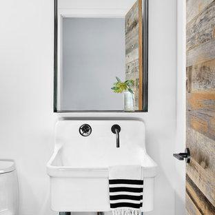 Industrial Gästetoilette mit weißer Wandfarbe, Waschtischkonsole, dunklem Holzboden, schwarzem Boden und weißer Waschtischplatte in Austin