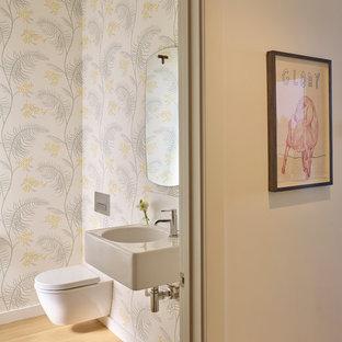 Esempio di un piccolo bagno di servizio chic con WC sospeso, pareti multicolore, parquet chiaro, lavabo sospeso e pavimento beige
