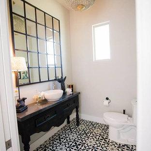 Пример оригинального дизайна: туалет среднего размера в стиле кантри с фасадами островного типа, черными фасадами, раздельным унитазом, бежевыми стенами, полом из цементной плитки, настольной раковиной, столешницей из бетона и разноцветным полом