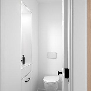 Стильный дизайн: маленький туалет в современном стиле с плоскими фасадами, белыми фасадами, инсталляцией, белыми стенами, полом из керамогранита, врезной раковиной, столешницей из ламината, коричневым полом и белой столешницей - последний тренд