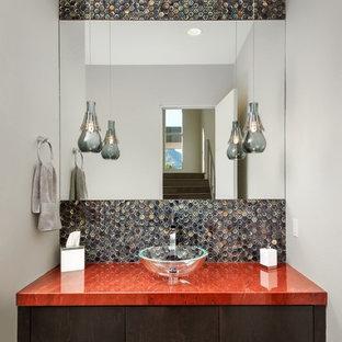 Modern inredning av ett mellanstort röd rött badrum, med släta luckor, skåp i mörkt trä, flerfärgad kakel, vita väggar, mellanmörkt trägolv, ett fristående handfat, granitbänkskiva och mosaik