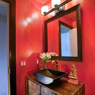 Exemple d'un petit WC et toilettes asiatique avec un placard en trompe-l'oeil, des portes de placard en bois vieilli, un mur rouge, un sol en bois brun, une vasque, un plan de toilette en bois et un sol marron.