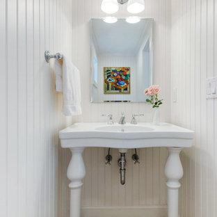 Пример оригинального дизайна: маленький туалет в морском стиле с раковиной с пьедесталом, унитазом-моноблоком, белыми стенами и полом из галечной плитки