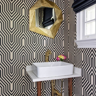 Powder room - mid-sized transitional dark wood floor and brown floor powder room idea in New York with multicolored walls, white countertops, open cabinets, a console sink and marble countertops