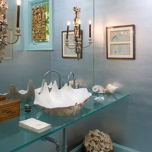 サンタバーバラのビーチスタイルのおしゃれなトイレ・洗面所 (ベッセル式洗面器、ガラスの洗面台、ターコイズの洗面カウンター) の写真