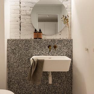 モントリオールのコンテンポラリースタイルのおしゃれなトイレ・洗面所 (モノトーンのタイル、セラミックタイル、白い壁、壁付け型シンク、マルチカラーの床、レンガ壁) の写真