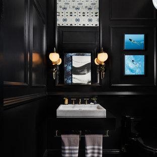 Diseño de aseo clásico con sanitario de dos piezas, paredes multicolor, lavabo suspendido y suelo azul