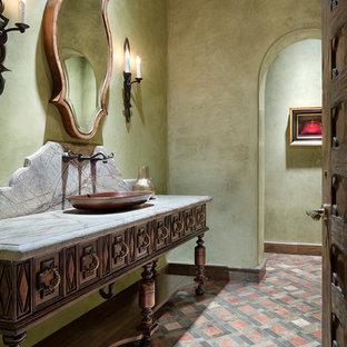 Стильный дизайн: огромный туалет в средиземноморском стиле с фасадами островного типа, фасадами цвета дерева среднего тона, зелеными стенами, мраморным полом, настольной раковиной, мраморной столешницей, разноцветным полом и разноцветной столешницей - последний тренд