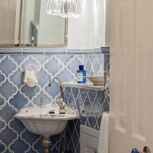 Стильный дизайн: маленький туалет в викторианском стиле с синей плиткой, керамической плиткой, белыми стенами и подвесной раковиной - последний тренд