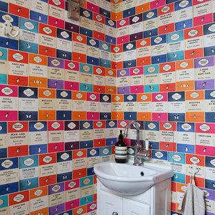 Cette image montre un petit WC et toilettes minimaliste avec un lavabo de ferme, des portes de placard blanches, un WC à poser, un mur multicolore et un placard avec porte à panneau encastré.