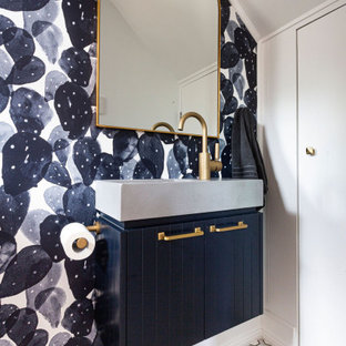 Inspiration for a contemporary powder room in Sydney with raised-panel cabinets, blue cabinets, white walls, an integrated sink, multi-coloured floor, grey benchtops, a built-in vanity, vaulted and wallpaper.