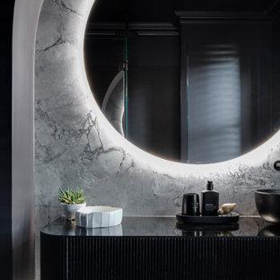 Пример оригинального дизайна: маленький туалет в стиле модернизм с фасадами с выступающей филенкой, черными фасадами, инсталляцией, черной плиткой, керамической плиткой, черными стенами, мраморным полом, настольной раковиной, стеклянной столешницей, серым полом, черной столешницей и подвесной тумбой
