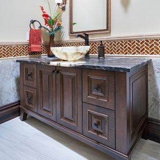カルガリーのラスティックスタイルのおしゃれなトイレ・洗面所 (レイズドパネル扉のキャビネット、濃色木目調キャビネット、ベージュのタイル、磁器タイル、ベージュの壁、磁器タイルの床、ベッセル式洗面器、御影石の洗面台、ベージュの床) の写真