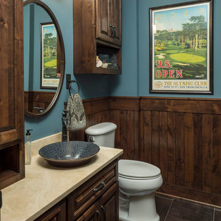 Inspiration for a rustic gray floor powder room remodel in Minneapolis with raised-panel cabinets, dark wood cabinets, blue walls and a vessel sink
