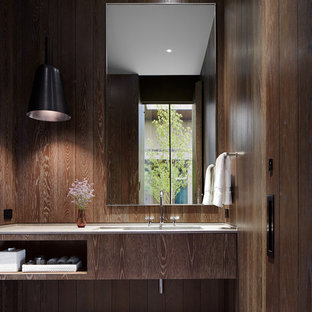 Example of a minimalist white tile limestone floor and gray floor powder room design in Denver with flat-panel cabinets, medium tone wood cabinets, an integrated sink, limestone countertops and brown walls