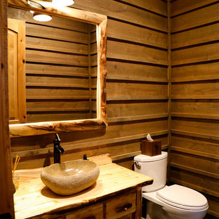 Photo of a rustic cloakroom in Salt Lake City with slate flooring, wooden worktops, freestanding cabinets, medium wood cabinets, a two-piece toilet, a vessel sink and multi-coloured floors.