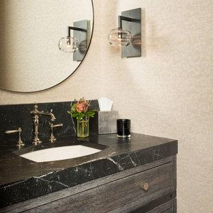 Modelo de aseo clásico renovado, de tamaño medio, con armarios tipo mueble, puertas de armario con efecto envejecido, sanitario de una pieza, paredes beige, suelo de madera en tonos medios, lavabo bajoencimera, encimera de esteatita y suelo marrón