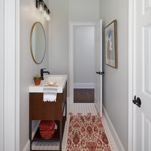 Powder room - mid-sized industrial mosaic tile floor and white floor powder room idea in Charlotte with furniture-like cabinets, dark wood cabinets, gray walls, an integrated sink, solid surface countertops and white countertops