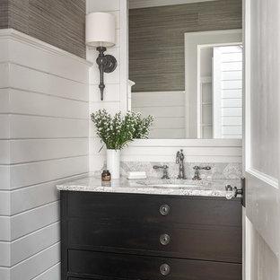 Aménagement d'un WC et toilettes bord de mer de taille moyenne avec un plan de toilette en quartz modifié, un placard en trompe-l'oeil, des portes de placard marrons, un mur multicolore, un sol en bois brun, un lavabo encastré et un plan de toilette gris.