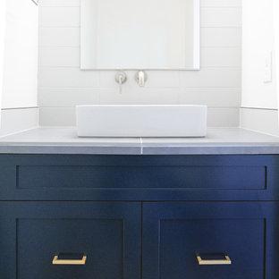 Cette image montre un petit WC et toilettes design avec un placard avec porte à panneau encastré, des portes de placard bleues, un carrelage blanc, des carreaux de céramique, un mur blanc, une grande vasque, un plan de toilette en surface solide et un plan de toilette gris.