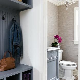 Cette photo montre un petit WC et toilettes chic avec un placard avec porte à panneau encastré, des portes de placard grises, un WC séparé, un carrelage beige, un mur beige, un sol en carrelage de porcelaine, un lavabo encastré et un plan de toilette en quartz.