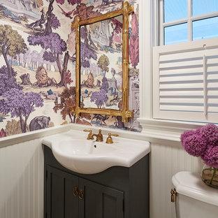 Inspiration pour un WC et toilettes traditionnel avec un lavabo intégré, un placard en trompe-l'oeil, des portes de placard noires, un mur multicolore et un sol en brique.