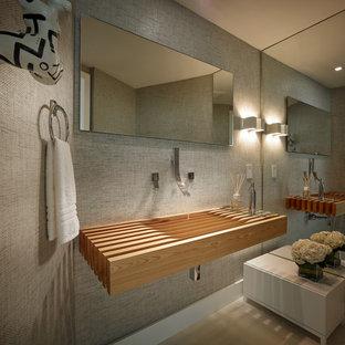 Foto di un piccolo bagno di servizio minimal con pareti grigie, pavimento in gres porcellanato, lavabo integrato, top in legno, pavimento beige e top marrone