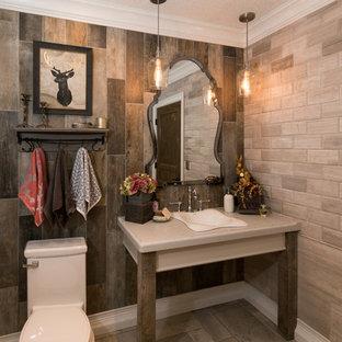 オレンジカウンティの大きいラスティックスタイルのおしゃれなトイレ・洗面所 (一体型トイレ、茶色いタイル、オーバーカウンターシンク、磁器タイル、グレーの壁、グレーの床、グレーの洗面カウンター) の写真