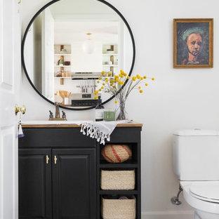 Cette image montre un WC et toilettes bohème avec un placard avec porte à panneau surélevé, des portes de placard noires, un mur blanc, un lavabo posé et un sol multicolore.