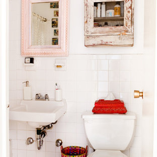 Example of an eclectic white tile powder room design in New York with a wall-mount sink