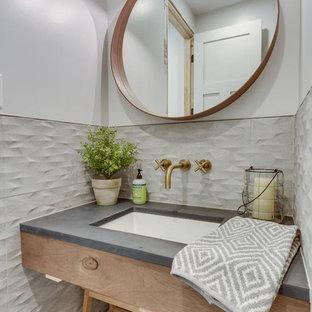 Foto på ett litet amerikanskt grå toalett, med skåp i ljust trä, vita väggar, ett undermonterad handfat, grå kakel, porslinskakel, klinkergolv i porslin och bänkskiva i betong