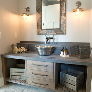 Cette image montre un WC et toilettes rustique de taille moyenne avec un placard à porte plane, des portes de placard en bois brun, un mur gris, un sol en carrelage de céramique, une vasque, un plan de toilette en zinc et un sol gris.
