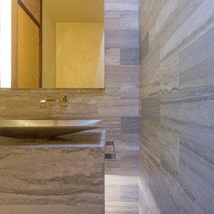 Inspiration pour un petit WC et toilettes design avec un mur gris, un sol en galet, une vasque et du carrelage en travertin.