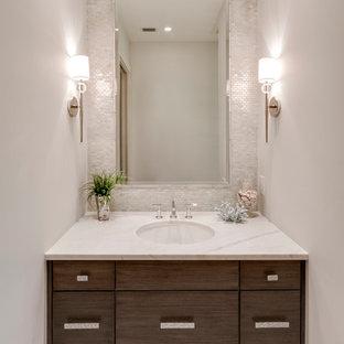Idée de décoration pour un WC et toilettes marin avec un lavabo encastré, un placard à porte plane, des portes de placard en bois sombre, un plan de toilette en quartz modifié, un carrelage gris, carrelage en mosaïque, un mur blanc et un plan de toilette blanc.