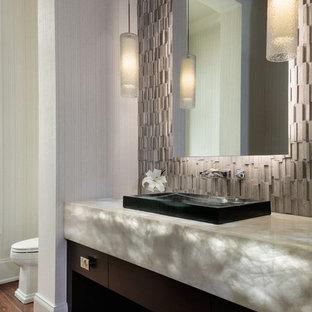 Cette photo montre un WC et toilettes tendance de taille moyenne avec un placard à porte plane, des portes de placard marrons, un sol en carrelage de céramique, un plan de toilette en onyx, un sol marron, un carrelage gris, un mur gris, une vasque et un plan de toilette gris.