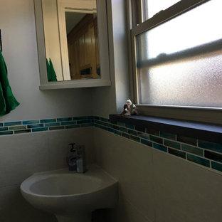 На фото: маленький туалет в морском стиле с стеклянными фасадами, белыми фасадами, раздельным унитазом, синей плиткой, стеклянной плиткой, черными стенами, полом из керамогранита, раковиной с пьедесталом, столешницей из талькохлорита, бежевым полом и черной столешницей