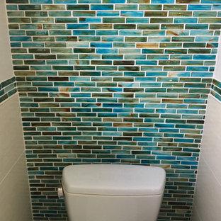 Неиссякаемый источник вдохновения для домашнего уюта: маленький туалет в морском стиле с стеклянными фасадами, белыми фасадами, раздельным унитазом, синей плиткой, стеклянной плиткой, черными стенами, полом из керамогранита, раковиной с пьедесталом, столешницей из талькохлорита, бежевым полом и черной столешницей