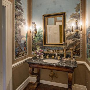 Cette photo montre un WC et toilettes chic de taille moyenne avec un lavabo encastré, un plan de toilette en onyx, un WC à poser, un carrelage gris, un mur multicolore et un sol en bois brun.