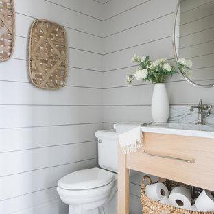 Imagen de aseo tradicional renovado con armarios con paneles lisos, puertas de armario de madera clara, sanitario de dos piezas, paredes blancas, suelo de madera oscura, lavabo bajoencimera, suelo marrón y encimeras grises