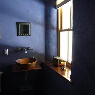Bild på ett litet rustikt toalett, med bänkskiva i koppar och ett fristående handfat